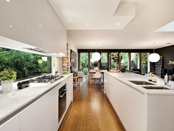 acabamento brilhante e sem puxadores, armários até o teto, vidro na parede da pia (iluminação)