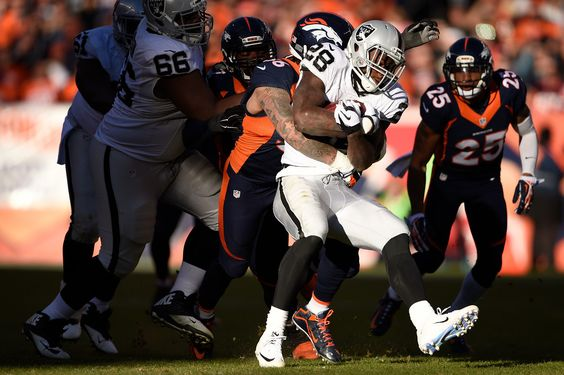 . DENVER, CO - DECEMBER 13: Shane Ray (56) of the Denver Broncos wraps up Latavius Murray (28) of the Oakland Raiders after a gain of 1 yard in the second quarter. The Broncos played the Oakland Raiders at Sports Authority Field at Mile High in Denver, CO on December 13, 2015. (Photo by Joe Amon/The Denver Post)