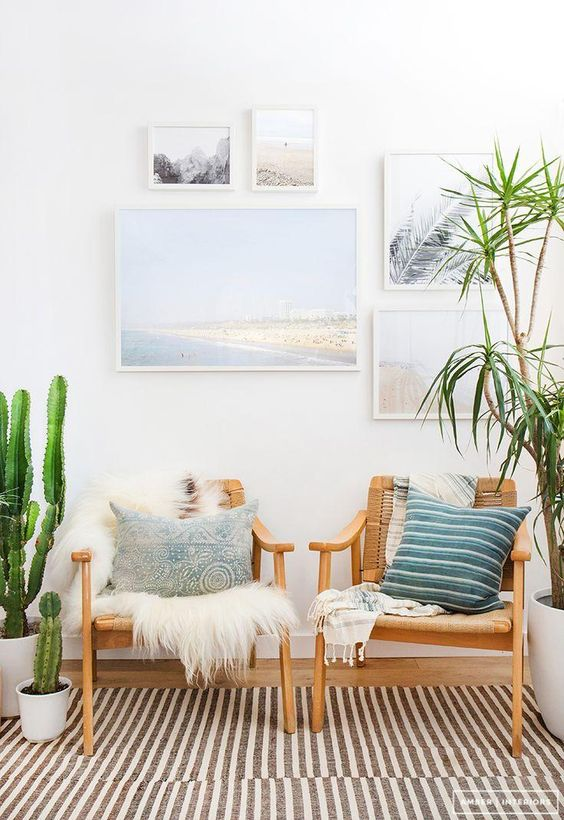 This gorgeous corner designed by Amber Interiors has the perfect California- Southwest desert feel. Blonde wood midcentury armchairs, vintage indigo mudcloth and batik pillows, sheepskin draped on the chairs, cactus and ponytail palm indoor potted plants, and gorgeous soft hued white framed prints in the gallery wall. Gorgeous!: