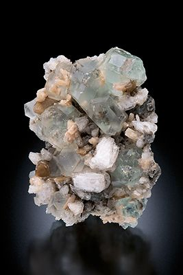 Transparent pale green fluorite crystals with periclase, mica, and schorl on albite, Pakistan