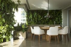 GREEN DINING AREA |  a dining area full of greenery gives the impression of being outdoors | bocadolobo.com/ #diningroomdecorideas #moderndiningrooms