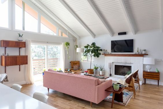I adore this bright living area. The couch offers the perfect pop of color to the white and neutral themed space.