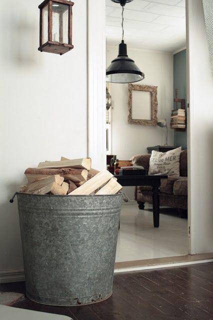a big metal bucket to store firewood #fireWoodStorage #firewoodrack #firewood #firewoodideas #organization #bucket
