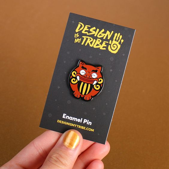 Pig The Shisa hard enamel pin with a black nickel finish by Chay Land #designismytribe