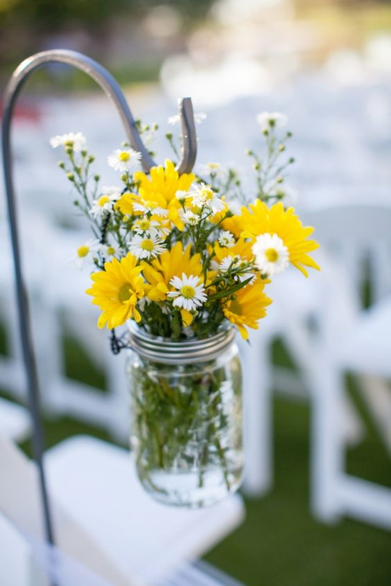 Simple, cheery flowers in mason jars lining the aisle. image: Ryan Nicole Photography