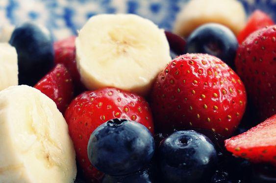bodegón de frutos rojos, fresas y arándanos, con rodajas de plátano