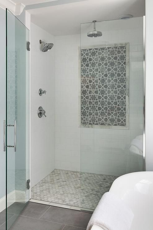White subway tiles accented with multi finish, gray dolomite, star pattered, Isidore marble mosaic tiles from Afyon line the walls of the this walk in shower boasting staggered gray tiled floors leading to a glass shower doors showcasing a circular, wall mounted shower head and a rain shower head hung over carrera marble hex shower floor tiles.