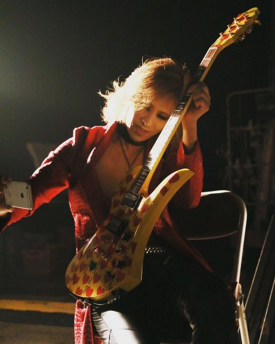黄色と赤の柄のギターを持って自撮りをしているXJAPAN・YOSHIKIの画像