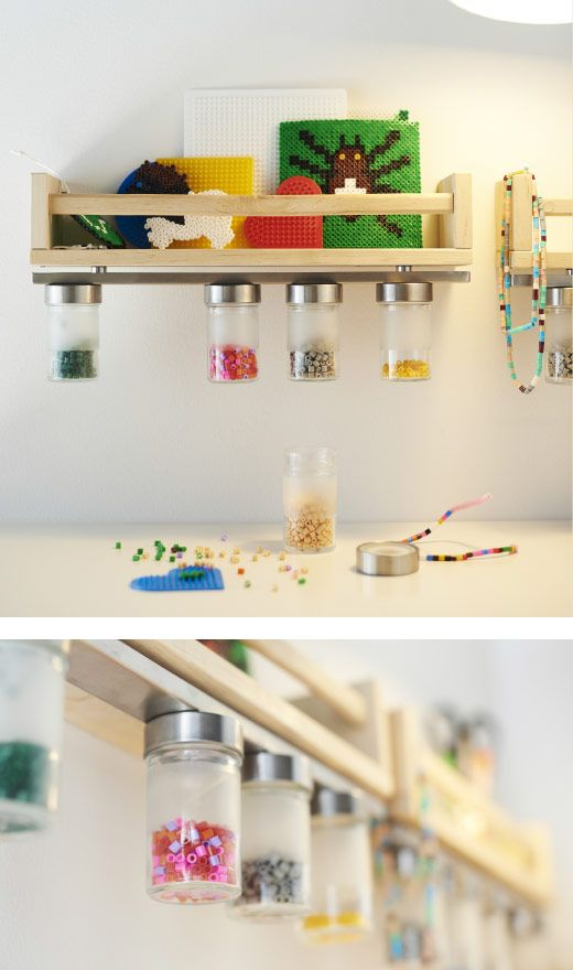 A small wooden shelf with a magnetic knife rack attached to the underside holds jars filled with beads.