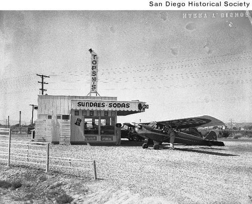 An airplane parked next to a Topsy's Drive-in at Pacific Highway and Hawthorne Street. (San Diego, Ca. c.1939)