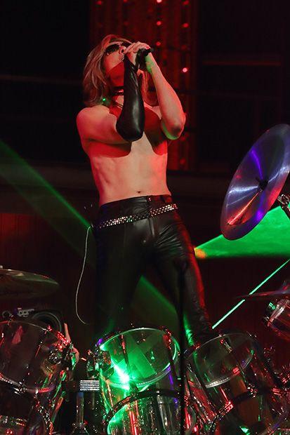 上半身裸でドラムセットの前でマイクパフォーマンスをしているXJAPAN・YOSHIKIの画像