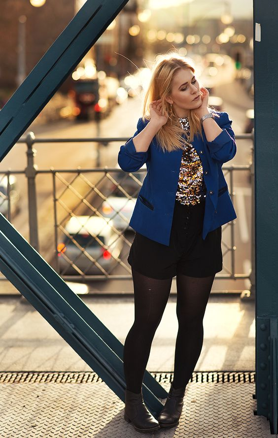Christina Key is wearing a sexy and edgy fashion look with a black shorts and a blue blazer in the style of the 80ies