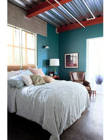 off the Chinese red of the beams, in Benjamin Moore's Million Dollar Red, Neunsinger painted the walls turquoise — Benjamin Moore's Jade Garden. Bedding and pillows are from Shabby Chic. Vintage