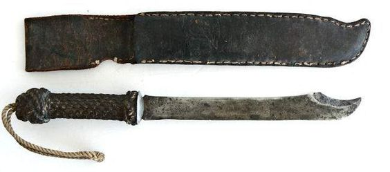 sailor made knife with a fancy rope work hilt and longer than usual blade of 9 14 inches. The blade and 2 inch false edge are sharpened to an extreme. The hilt is covered with woven rope to prevent slipping and embellished with a Turks Head at each end, all painted brown. There is a long lanyard out the end to keep the knife from being dropped. The original hand tooled leather scabbard has a small atoll with large palm tree and single native figure on its face. All the metal work