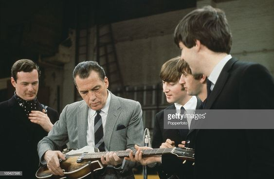 Members of the Beatles, and their manager Brian Epstein (1934 - 1967), look on as American TV host Ed Sullivan (1901 - 1974) tries out Paul's Hofner violin bass during rehearsals for the Ed Sullivan Show at the Ed Sullivan Theater, New York, February 1964. Left to right: Epstein, Sullivan, John Lennon (1940 - 1980), Ringo Starr and Paul McCartney.