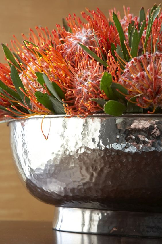 Exotic protea + polished hammered bowl = modern, natural chic.