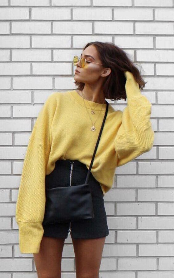 Como usar amarelo em diversos looks: guia completo. Moletom oversized, saia de couro preta, bolsa preta