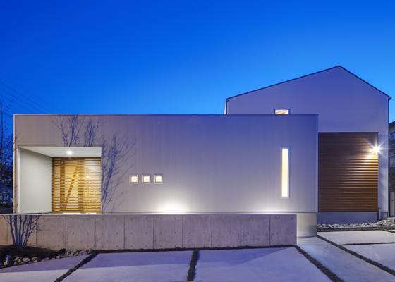 玄関の格子戸や窓から漏れる光が印象的です 専門家 が手掛けた 外観夜景 公園前の家 明るくて風通しの良い住宅 の詳細
