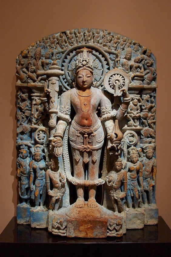 Stele with Vishnu and Other Hindu Deities, c. 1100, India: Uttar Pradesh, sandstone with indigo pigments.  This remarkable stele is dedicated to the great Hindu god Vishnu, the preserver and protector of the universe. He stands in the frontal samapada posture, holding four of his primary attributes: a large club and a solar disc or wheel in his upper hands and a rosary and conch shell in his lower hands. These symbolic emblems and weapons indicate his divine status, his association with the…