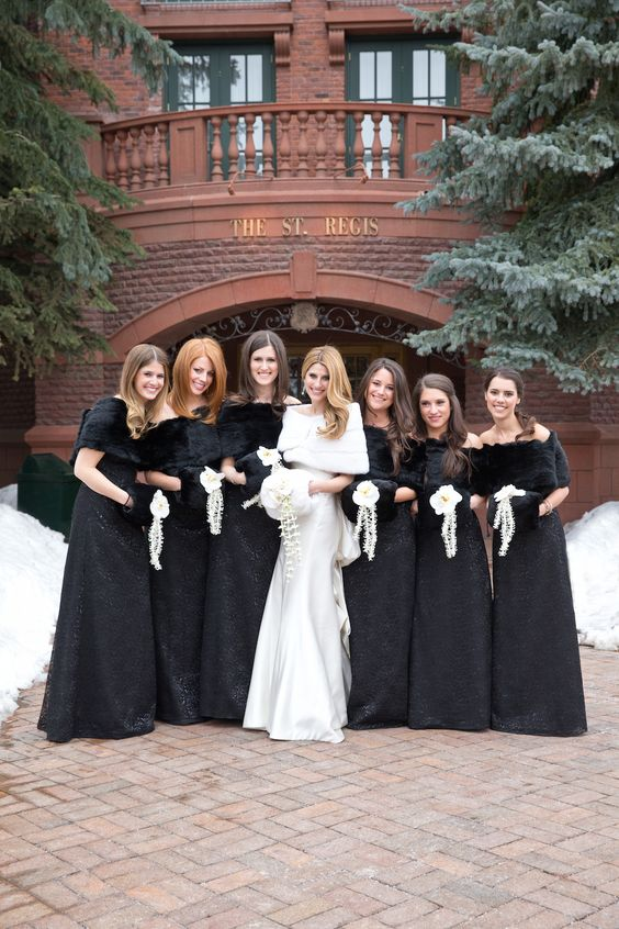 Bridesmaids accessorized their black floor-length gowns with fur shawls and muffs. #WinterWedding Photography: Aaron Delesie Photographer. Read More: http://www.insideweddings.com/weddings/snowy-spring-celebration-in-aspen-colorado/596/