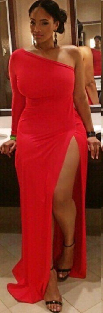 Vestido vermelho com fenda e sandálias de tiras pretas.