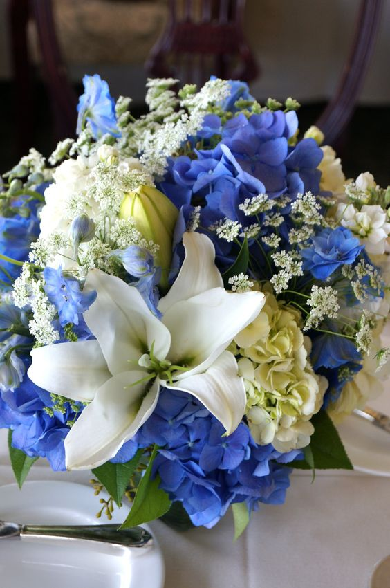 Blue and white bridal bouquet with lilies, hydrangea, queen anne's lace, and delphinium.