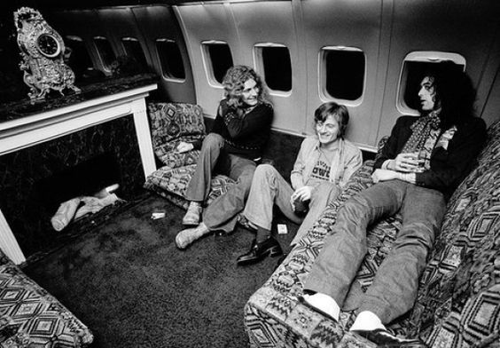 Led Zeppelin gather around a fireplace on their private jet The Starship during their tour of The States in 1975.