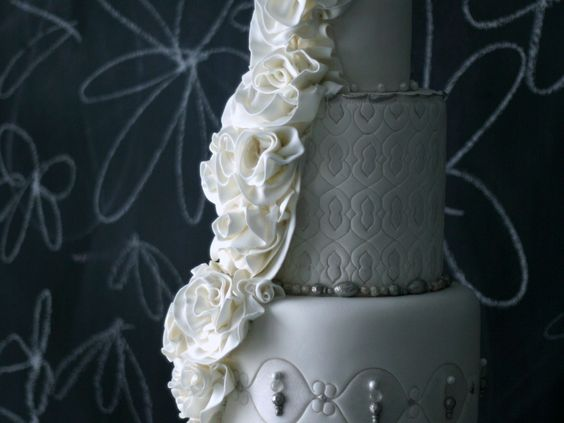 cake inspired by the rosettes on a Monique Lhuillier gown. Tons of edible bling bling was added to this towering wedding..  i like the bling and i like that the flowers are similar to the brides dress