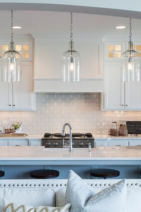A trio of Corsica Pendants illuminate an extra long kitchen island topped with white quartz fitted with a sink and gooseneck faucet lined with industrial metal and wood swivel counter stools.