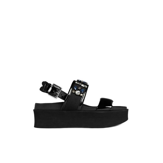 Sandalia anatómica de plataforma que se adapta perfectamente al pie gracias a la forma de su plantilla y piso. Realizada en piel con detalles de charol, nilon y pedrería. Plataforma de microgoma.
