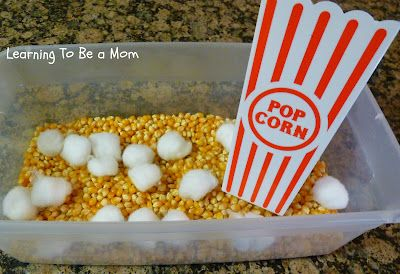 use tweezers to pick up cotton balls and place them in a popcorn box. good fine motor. ~also, could make a popcorn bin for scooping unpopped popcorn into the popcorn box.
