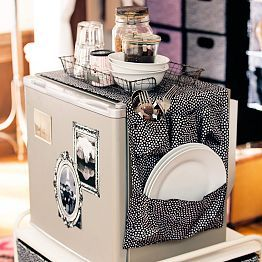 Hang a fabric storage unit over your mini fridge to hold utensils, dishware, dish soap, sponges, and more!