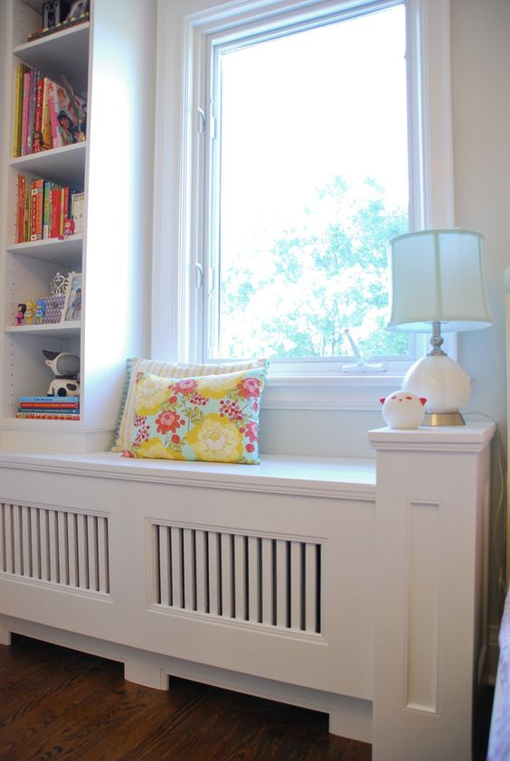 We're loving the way ramblingrenovators.ca turned an awkward corner radiator into a room focal-point with the addition of a custom slatted window bench and bookcase. | thisoldhouse.com: