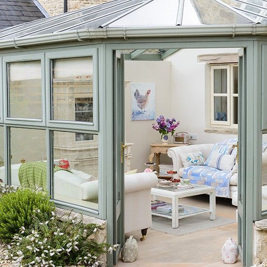 Green country conservatory with white walls and wooden flooring ...