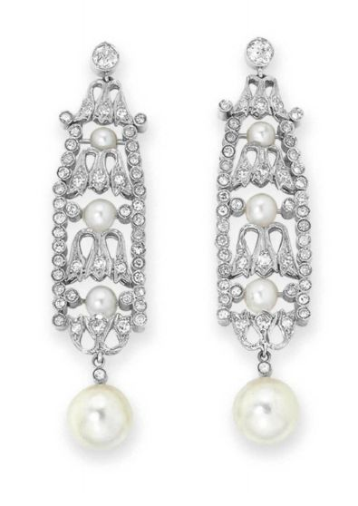 A PAIR OF BELLE EPOQUE PEARL AND DIAMOND EAR PENDANTS   Each suspending a button pearl, measuring approximately 9.16 and 8.88 mm, from an openwork single and old European-cut diamond panel, set at the center with three smaller pearls, mounted in platinum, circa 1915