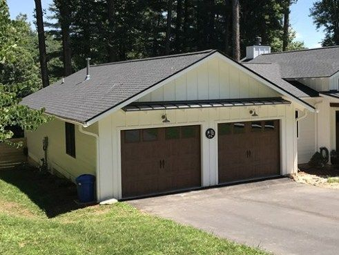 The Contrasting Paint On The Garage Doors Matches The Shingles The Metal Roof Over The Garage Doors A Farmhouse Style Lighting Farmhouse Style Metal Shed Roof
