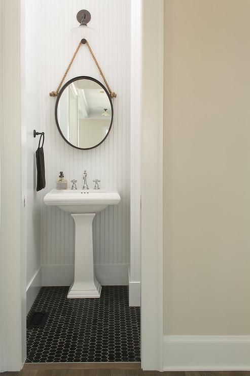 Black and white cottage powder room features a white beadboard wall lined with a glass vintage wall sconce illuminating an oval rope hung mirror and a pedestals ink atop black hex floor tiles.