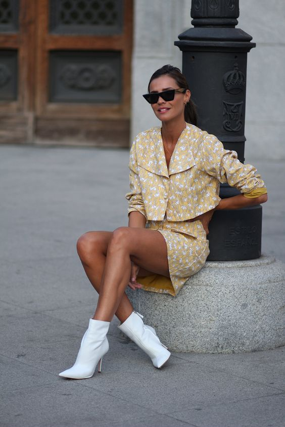 Yellow and white floral print crop top/ blouse and buttoned mini skirt+white heeled ankle boots+black sunglasses. Pre-Fall/ Transitional Dresy Casual Outfit 2018