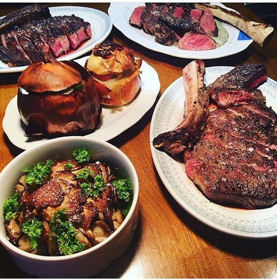 """Our """"Four Two section"""" is comprised of not only a half roasted pigs head, but an outstanding 52 day Dry Aged Tomahawk steak served with charred whole onion, alongside a pot of wood mushrooms! #sauvageny photo credit @spatrickmccarthy"""