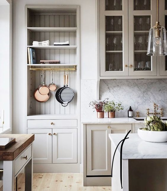 A serene farmhouse kitchen design with warm putty gray painted kitchen cabinets, beadboard, and marble backsplash in a gorgeous classic kitchen. #kitchendesign #greykitchen #farmhousekitchen #serene