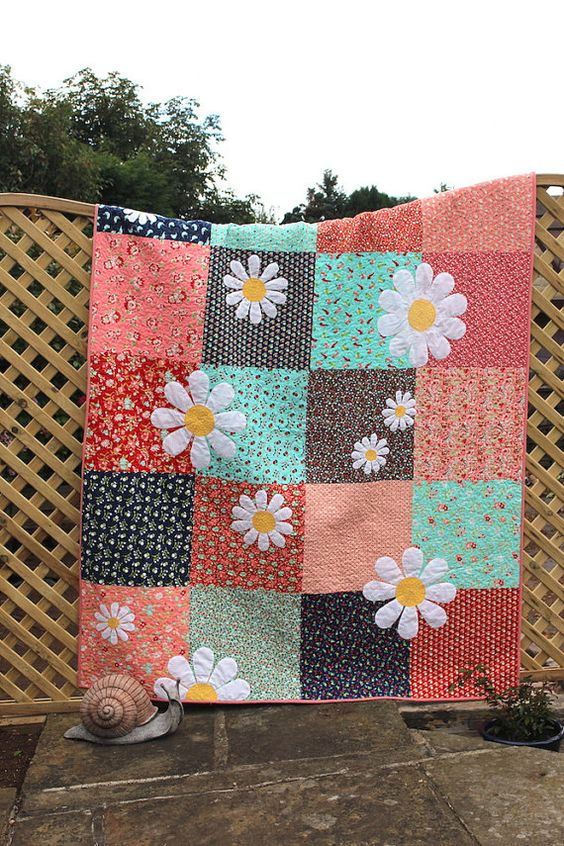 This Daisy Quilt is a great pattern for a beginner. Simple piecing and appliqué makes for a really visually popping quilt. Let your fabrics do the talking with this project. It is super pretty and just delicious for snuggling under. Bring a taste of summer into your home every