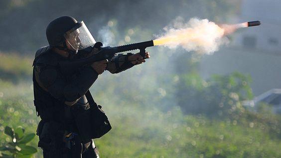 Policial lança bomba de gás lacrimogêneo contra manifestantes nas proximidades do estádio Castelão, em Fortaleza, onde Espanha e Itália jogaram semifinal da Copa das Confederações, na quarta feira (27)