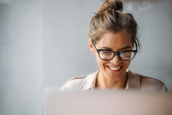 Close up of a woman with glasses working on computer.