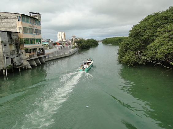 a boat navigating in the Rio Esmeraldas what divides the city in two