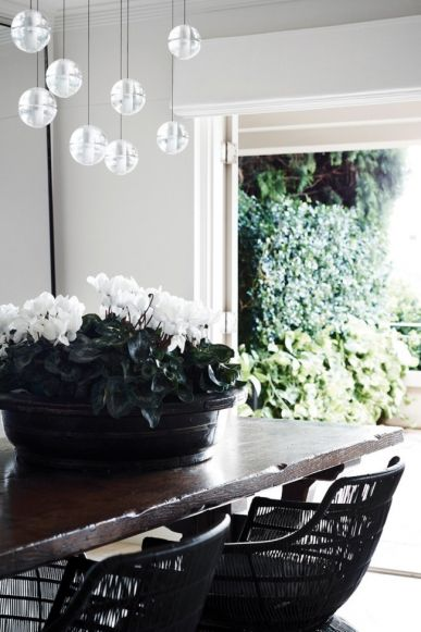 House tour: a lesson in layering by interior designer Pamela Makin: In the dining room, a black timber Chinese bowl from Les Interieurs sits atop a French oak dining table from Sally Beresford. Bocci pendant lights from Hub Furniture Lighting Living and B&B Italia 'Crinoline' dining chairs from Space Furniture add drama, while custom-made metal-framed mirrors from Les Interieurs enhance the sense of space.