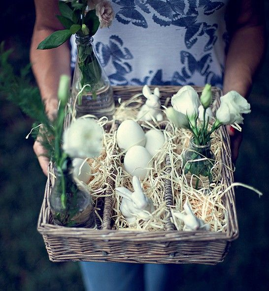 Com palha, ovos cozidos, coelhos de louça e flores em garrafas, o porta-talheres de vime vira um centro de mesa
