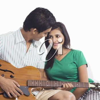 Man playing a guitar beside a woman