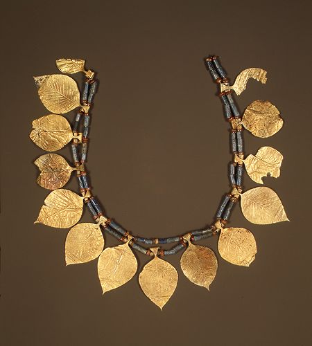 """2600-2500 BCE leaf-shaped headdress      Early Dynastic period IIIa; Sumerian style  Excavated at """"King's Grave,"""" Ur, Mesopotamia  Gold, lapis lazuli, carnelianthe city of Ur, in which sixteen royal tombs were excavated in the 1920s and 1930s by Sir Leonard Woolley.  L. 15 3/16 in. (38.5 cm) hb_33.35.3"""
