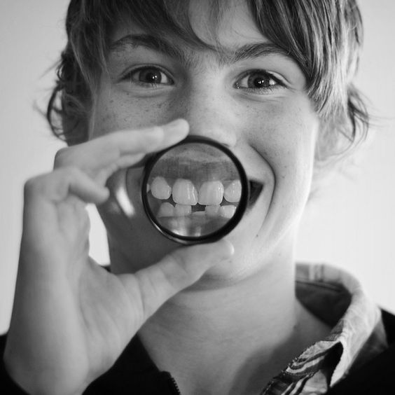 photo project idea: take b high-detail photos of my friends with magnifying glass in front of their smile. like this... but more definition/detail, and a larger mag glass.