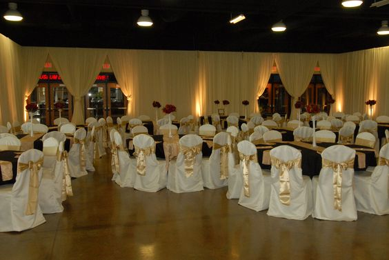 This wedding reception customer chose to drape the walls with a cream fabric to soften the room while using white chair covers with gold bows, black table cloths and gold napkins.